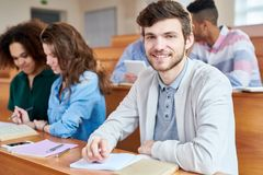Happy handsome guy in lecture room. Smiling positive handsome young male student with beard sitting at wooden desk together with groupmates and looking at camera Royalty Free Stock Photos