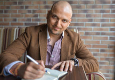 Happy handsome indian businessman making some notes in his notebook, business plan or diary writing.  Stock Image