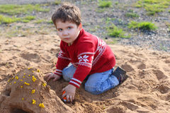 Happy handsome little boy plays in sand Royalty Free Stock Images