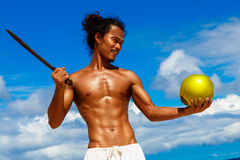 Happy handsome man of Asian appearance with coconut on the tropical beach on sunny summer day during holidays vacation. Tropical. Sea on the background royalty free stock image