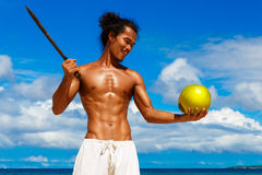 Happy handsome man of Asian appearance with coconut on the tropical beach on sunny summer day during holidays vacation. Tropical. Sea on the background royalty free stock images