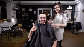 Happy handsome man in barbershop looking at himself in big mirror after hairstyling. Female barber is demonstrating to stock video