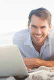 Happy handsome man on the beach with his laptop Stock Images