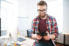 Happy handsome man with beard sitting and using tablet Royalty Free Stock Photos
