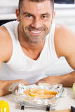 Happy handsome man cooking in kitchen at home. Stock Images