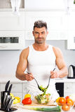 Happy handsome man cooking in kitchen at home. Royalty Free Stock Image