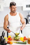 Happy handsome man cooking in kitchen at home. Royalty Free Stock Photos