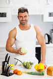 Happy handsome man cooking in kitchen at home. Stock Image