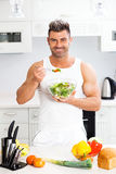 Happy handsome man cooking in kitchen at home. Stock Photos