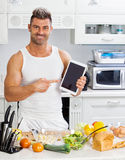 Happy handsome man cooking in kitchen at home. Royalty Free Stock Photo