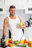 Happy handsome man cooking in kitchen at home. Royalty Free Stock Photography