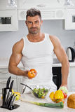 Happy handsome man cooking in kitchen at home. Royalty Free Stock Images