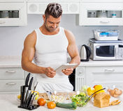 Happy handsome man cooking in kitchen at home. Stock Photography