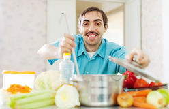 Happy handsome man cooks lunch Royalty Free Stock Image