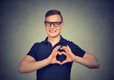 Happy handsome man in glasses making heart with fingers. Portrait of happy handsome man in glasses making heart with fingers Royalty Free Stock Images