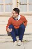 Happy handsome man with glasses and sweater sitting on steps in Royalty Free Stock Images