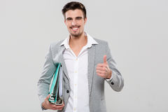 Happy handsome man holding binders and showing thumbs up Stock Photography