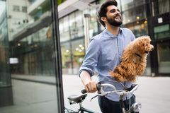Happy young man holding dog in hands outdoors in city. Happy handsome man holding dog in hands outdoors in city stock photos