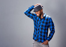 Happy handsome man laughing with hand to hat Stock Photos