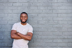 Happy handsome man leaning against gray wall Stock Images