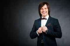 Happy handsome man with long hair brunette and brown eyes in dar. K suit with stripes and bow tie looking forward at black background Stock Photos