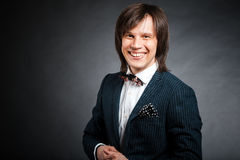 Happy handsome man with long hair brunette and brown eyes in dar. K suit with stripes and bow tie looking forward at black background Royalty Free Stock Photos
