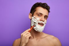 Happy handsome man looking at camera and shaving his face with razor stock image