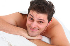 Happy handsome man lying in bed Stock Photos
