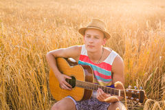 Happy handsome man is playing guitar in the field Royalty Free Stock Photos