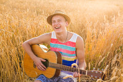 Happy handsome man is playing guitar in the field Stock Photography