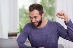 Happy Handsome Man Reading Good News at Laptop. Happy Handsome Man in Long Sleeve Shirt Reading Good News at Laptop Stock Image