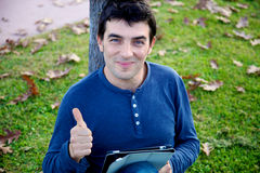 Man thumb up in park with tablet Royalty Free Stock Images