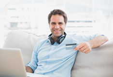 Happy handsome man sitting on sofa online shopping with laptop Royalty Free Stock Photography