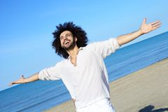 Happy handsome man smiling on the beach Stock Image