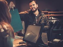 Happy handsome man taking shopping bag from saleswoman in a suit shop. Happy handsome men taking shopping bag from saleswoman in a suit shop royalty free stock image