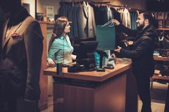 Happy handsome man taking shopping bag from saleswoman in a suit shop. Happy handsome men taking shopping bag from saleswoman in a suit shop royalty free stock images