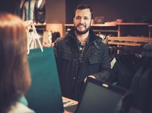 Happy handsome man taking shopping bag from saleswoman in a suit shop. Happy handsome men taking shopping bag from saleswoman in a suit shop stock image