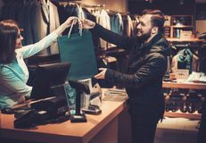 Happy handsome man taking shopping bag from saleswoman in a suit shop. Happy handsome men taking shopping bag from saleswoman in a suit shop stock images