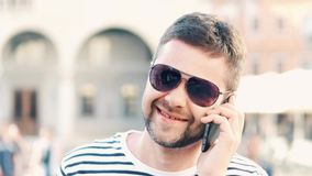 Happy handsome man talking on his cell phone on the street, close-up shot. Young handsome bearded man talking on his mobile phone Royalty Free Stock Images