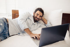 Happy handsome man using laptop. Lying on bed in bedroom. Stock Photography