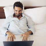Happy handsome man using laptop. Lying on bed in bedroom. Royalty Free Stock Image