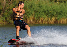 Happy handsome man wakesurfing stock photos