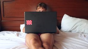 Happy handsome man working in bed in bright bedroom. 4k, slow motion stock video