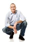 Happy handsome mature man squatting Stock Images