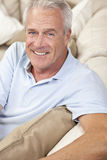 Happy Handsome Senior Man Smiling at Home. Happy and healthy senior man sitting on a sofa at home smiling and happy stock photography