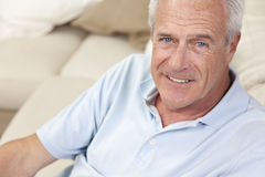 Happy Handsome Senior Man Smiling at Home. Happy and healthy senior man sitting on a sofa at home smiling and happy Stock Image