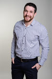 Happy handsome smiling man in fashionable shirt stands on a gray background Royalty Free Stock Images