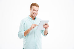 Happy handsome smiling young guy using tablet Royalty Free Stock Photo