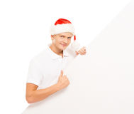 Happy and handsome teenage guy in a Christmas hat and a banner Stock Image