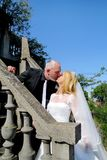 The happy handsome wedding couple are standing and kissing on stone steps in front of house. Wedding concept. The happy handsome wedding couple are standing and royalty free stock photography